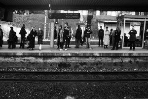 Passagers sur un quai, silhouettes indistinctes, comme des signes d'écriture sur une ligne.