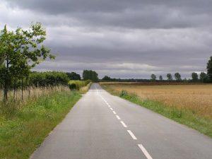 Route secondaire filant vers l'horizon, sous un plafond bas de nuages.