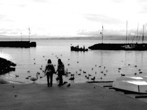 Deux personnes sur la plage d'un petit port de pêche.
